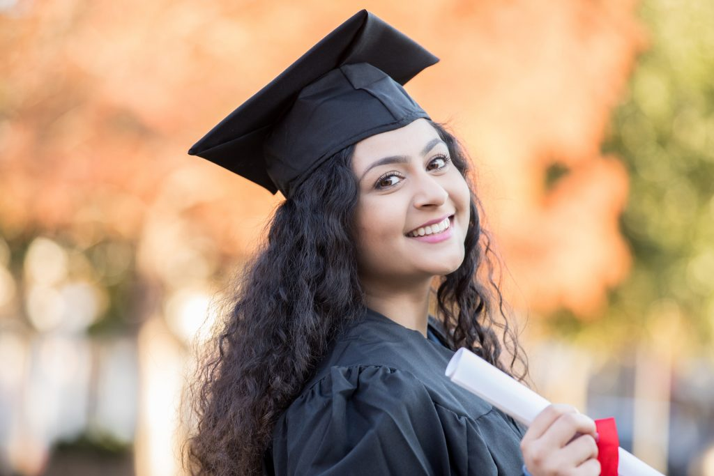 Young grad holding diploma
