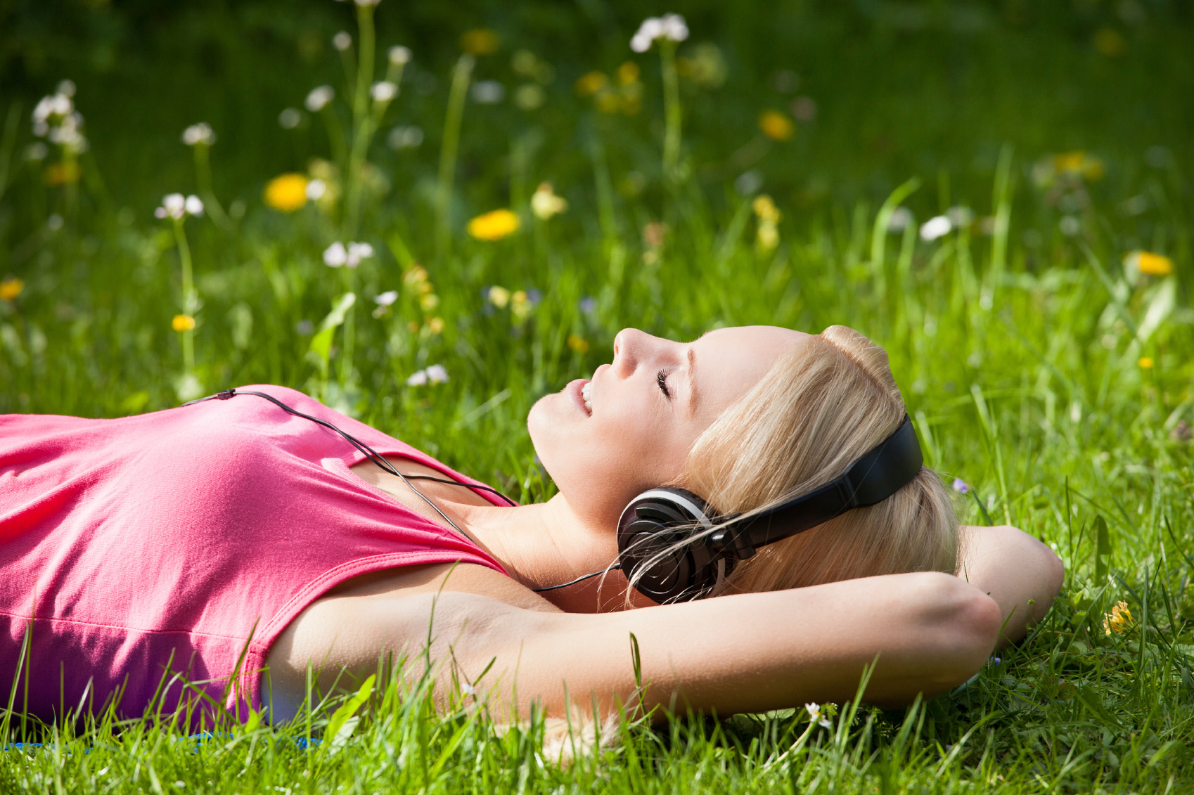 Young Woman Lying On Grass And Listening To Music With Headphones