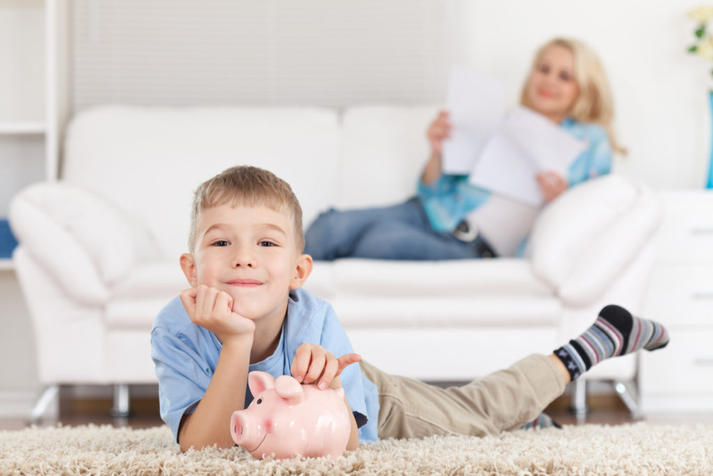 A little boy is laying on the floor and inserting a coin in the piggy bank. His mother is sitting on the couch. The focus of the image is on the little boy. The mother is holding two papers in her hands.