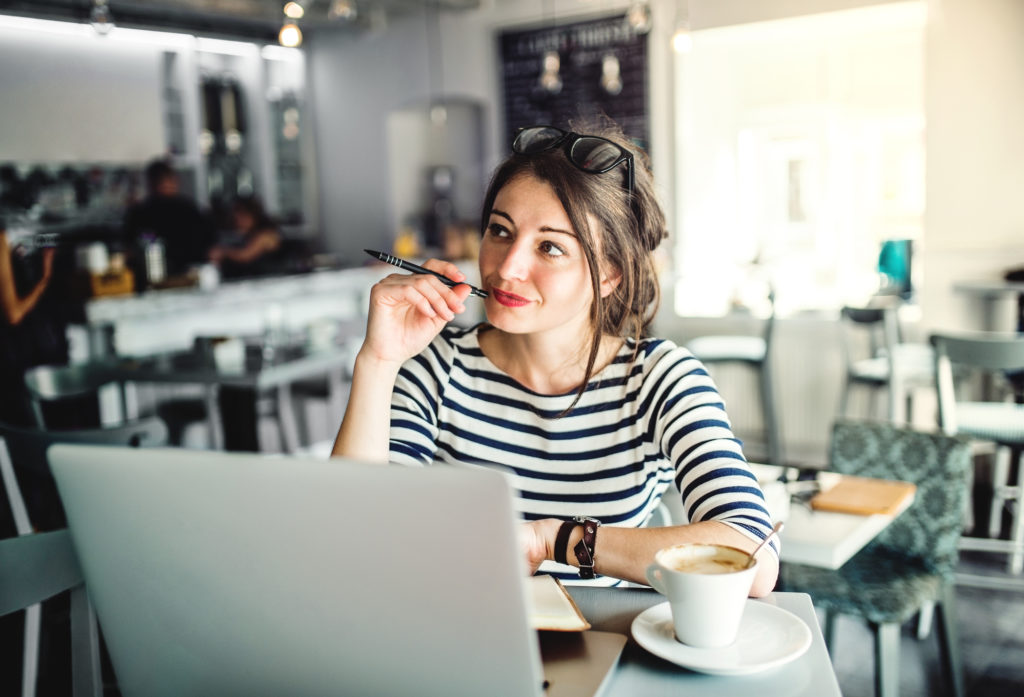 An attractive young woman with laptop and a cup of coffee sitting in a cafe, writing.