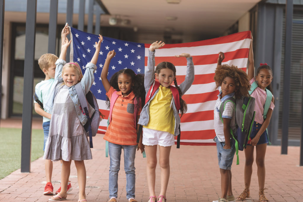 Happy school students standing in corridor while holding american flag