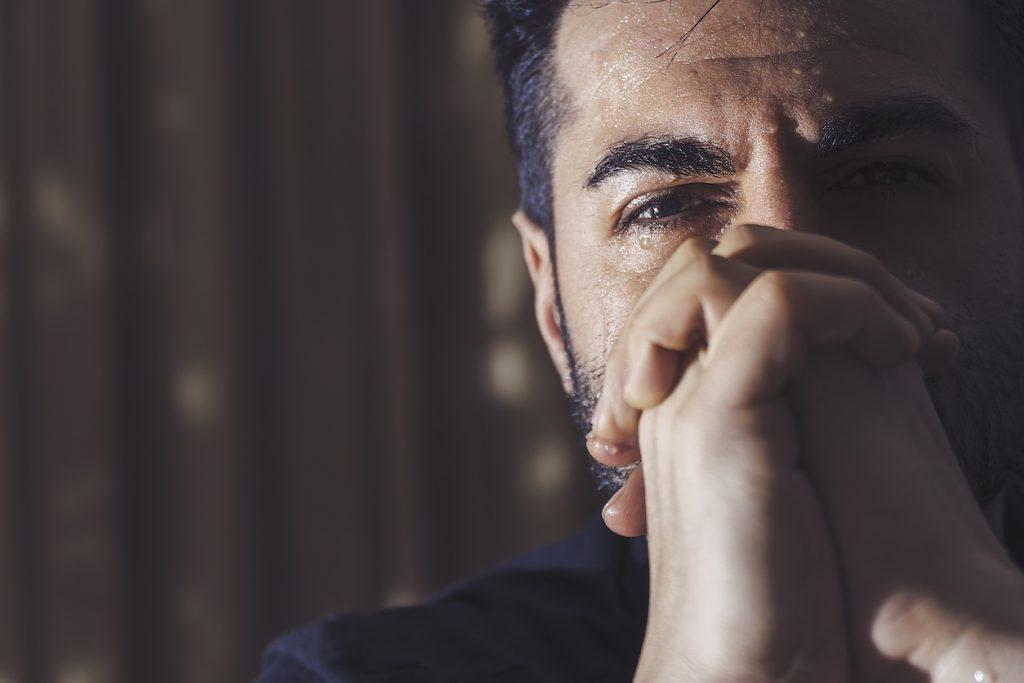 Depressed man praying, crying